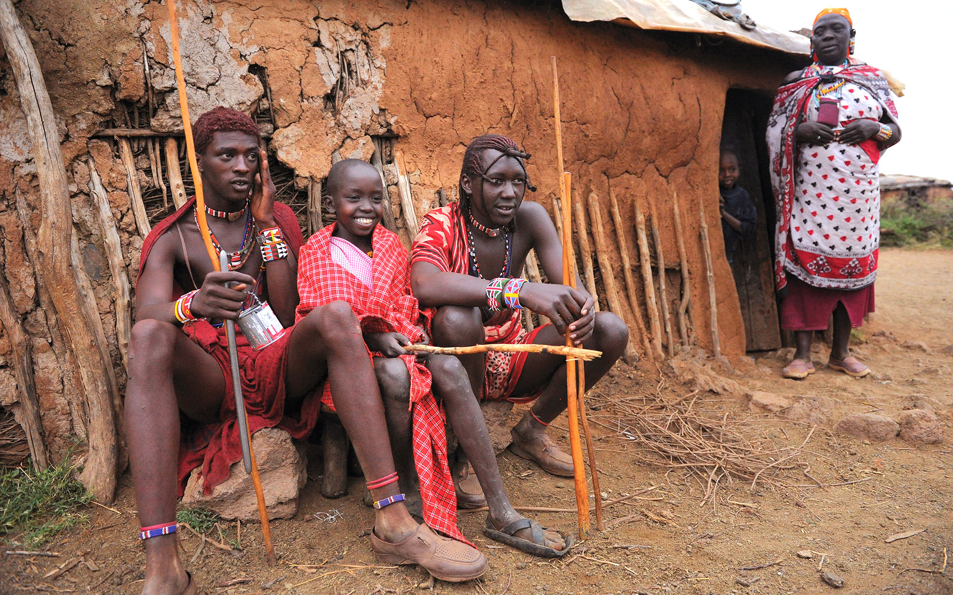 A Kenyan boy sits with two warriors from his village