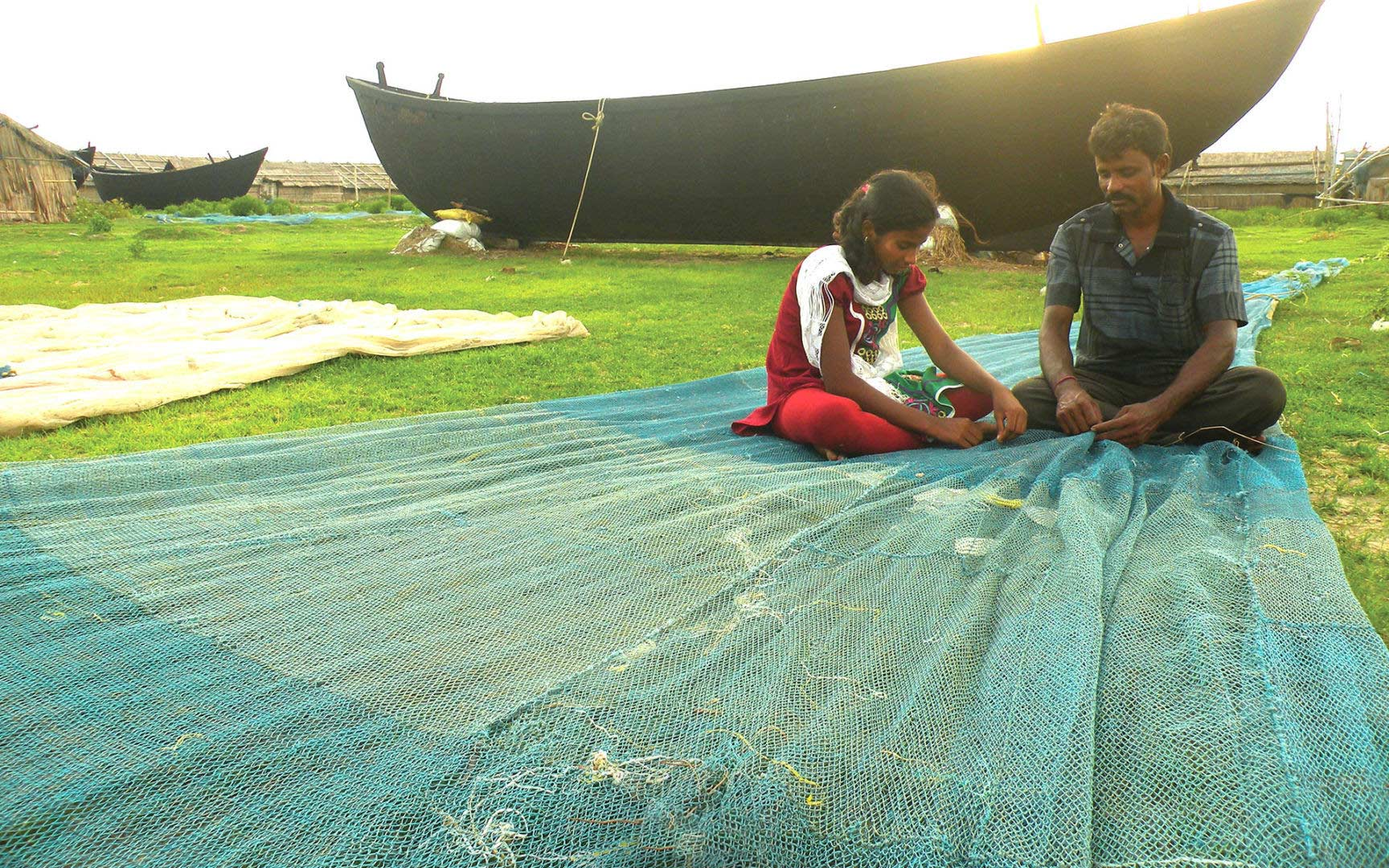 A girl helps her father mend a fishing net in eastern India