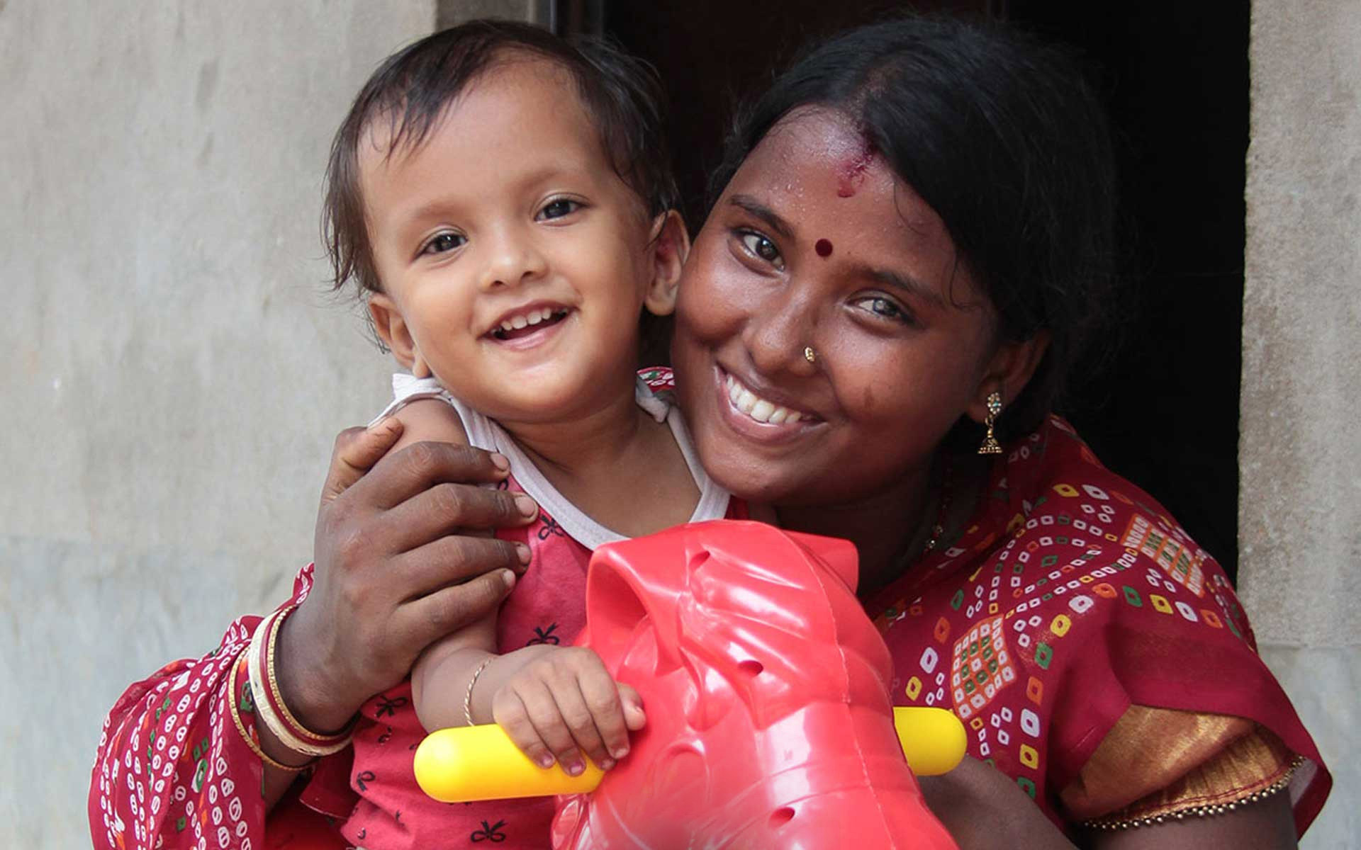 A mother plays with her daughter outside their home in India