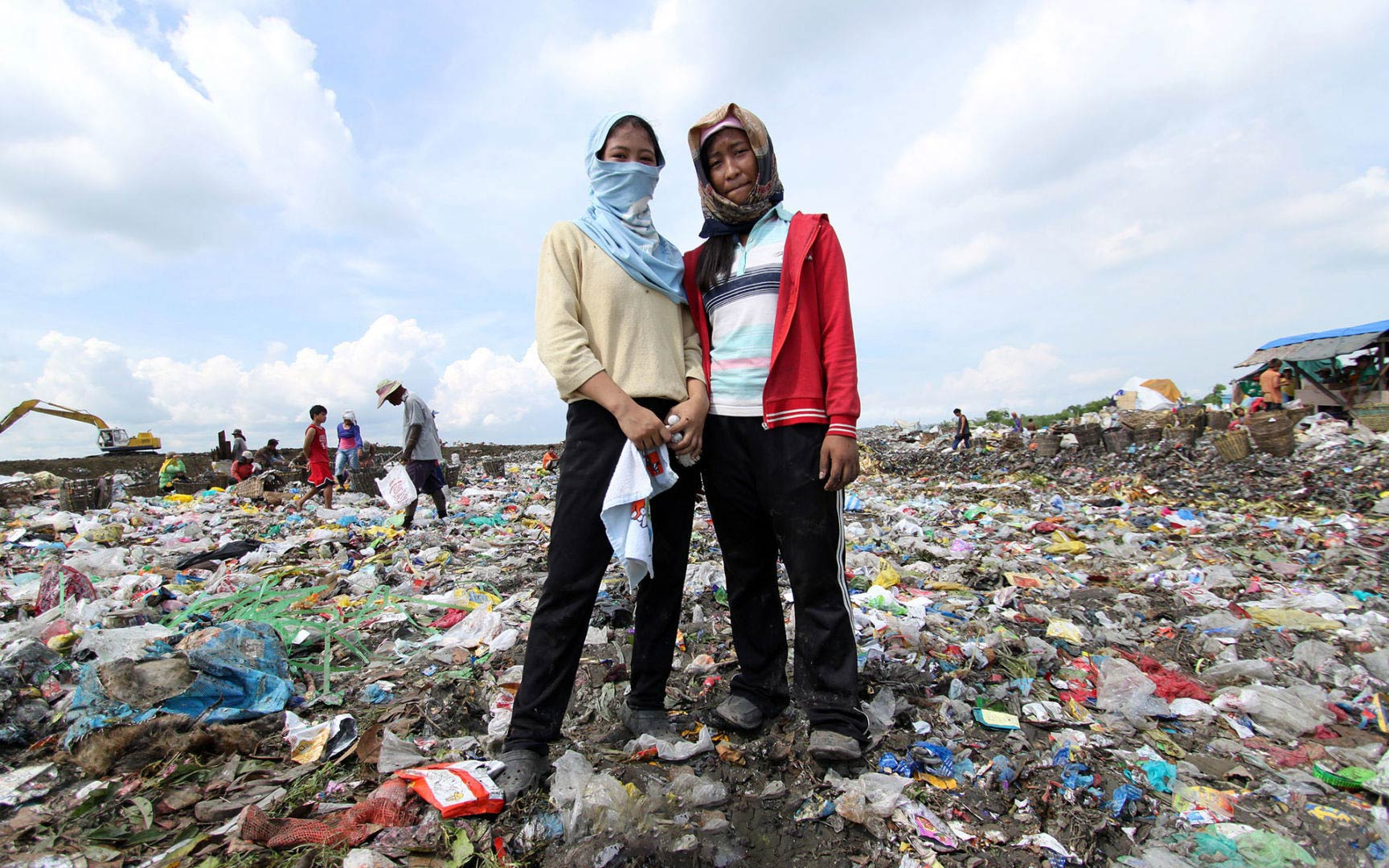 Sisters standing in the dump looking for items to use
