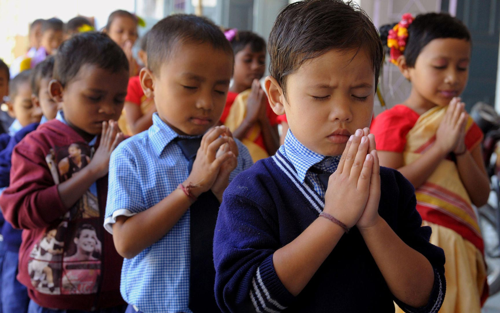 Children praying with their hands folded