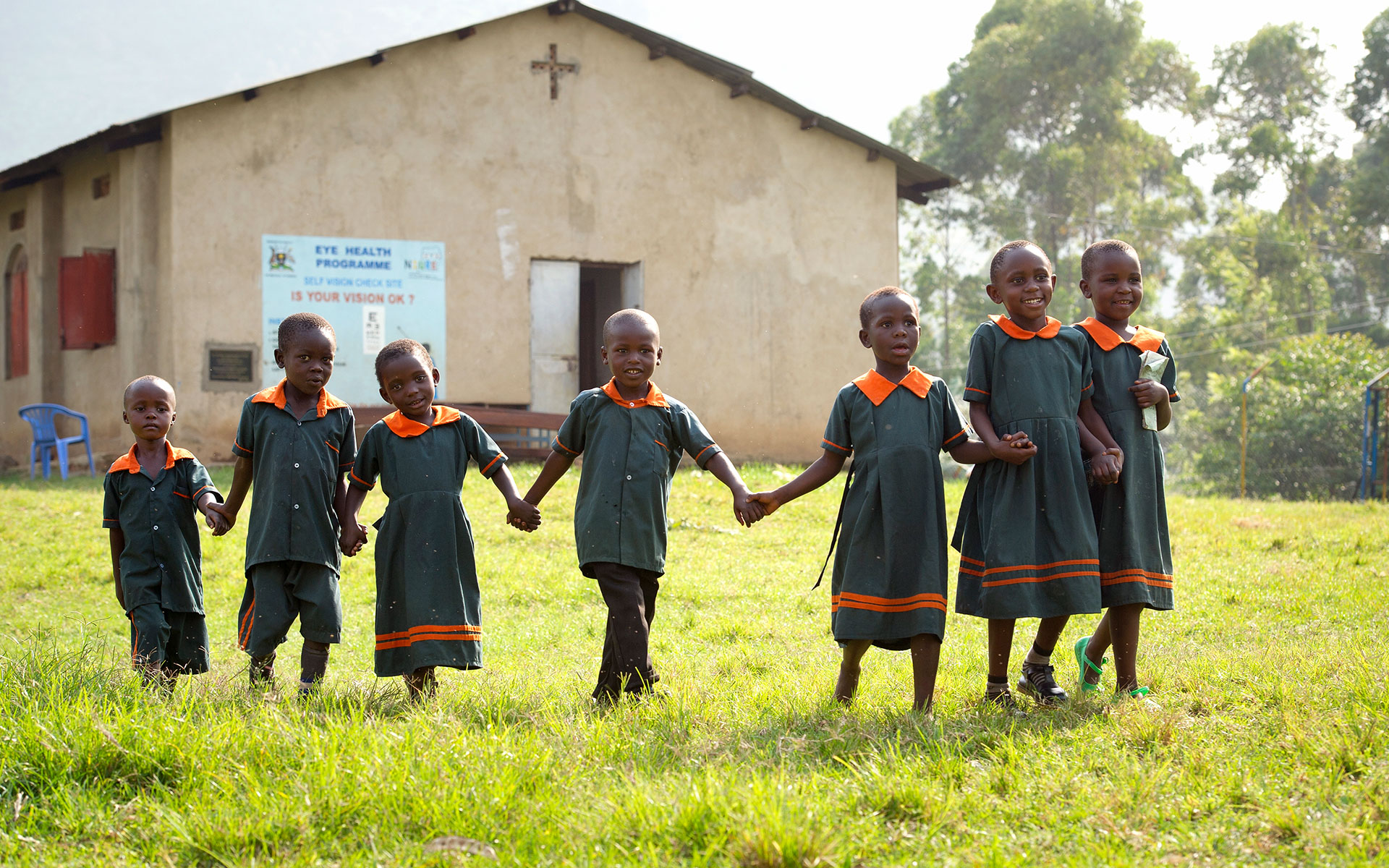 A group of children walks in the grass beside a Compassion center