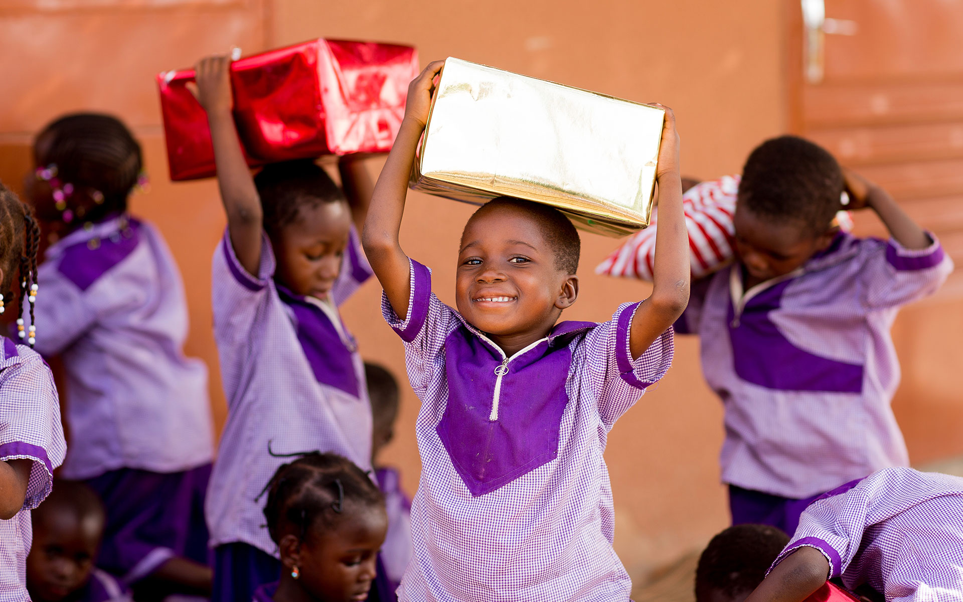 A child in Burkina Faso smiles as he receives a Christmas gift