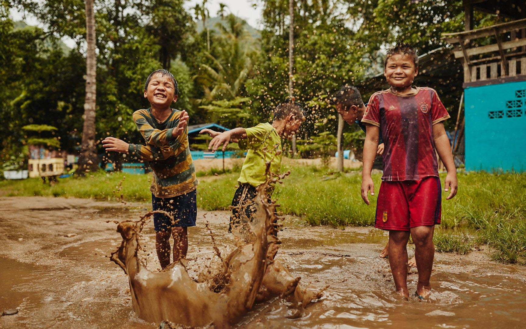 Kids spash in a mud puddle and laugh