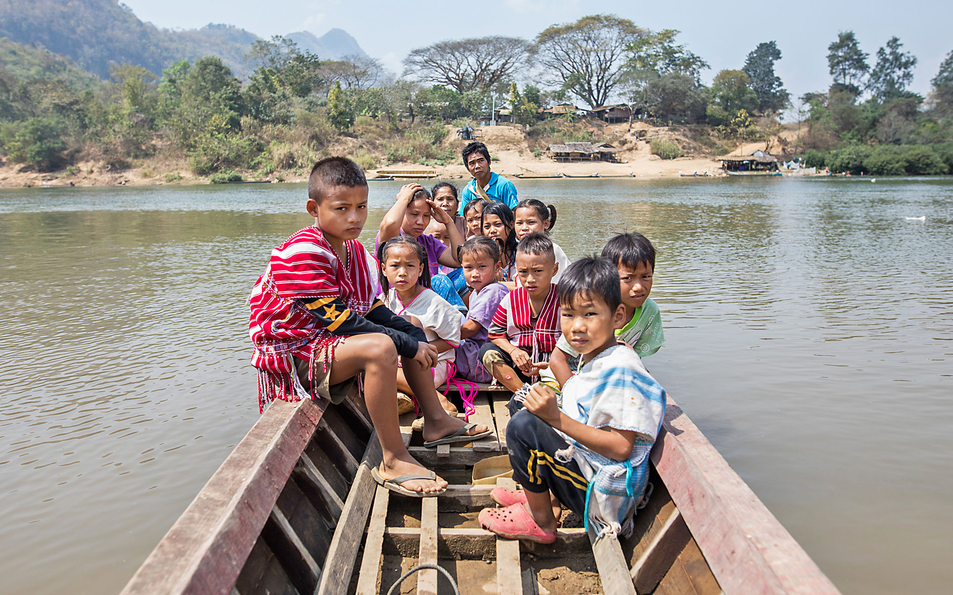 A large family and children sit in a small boat