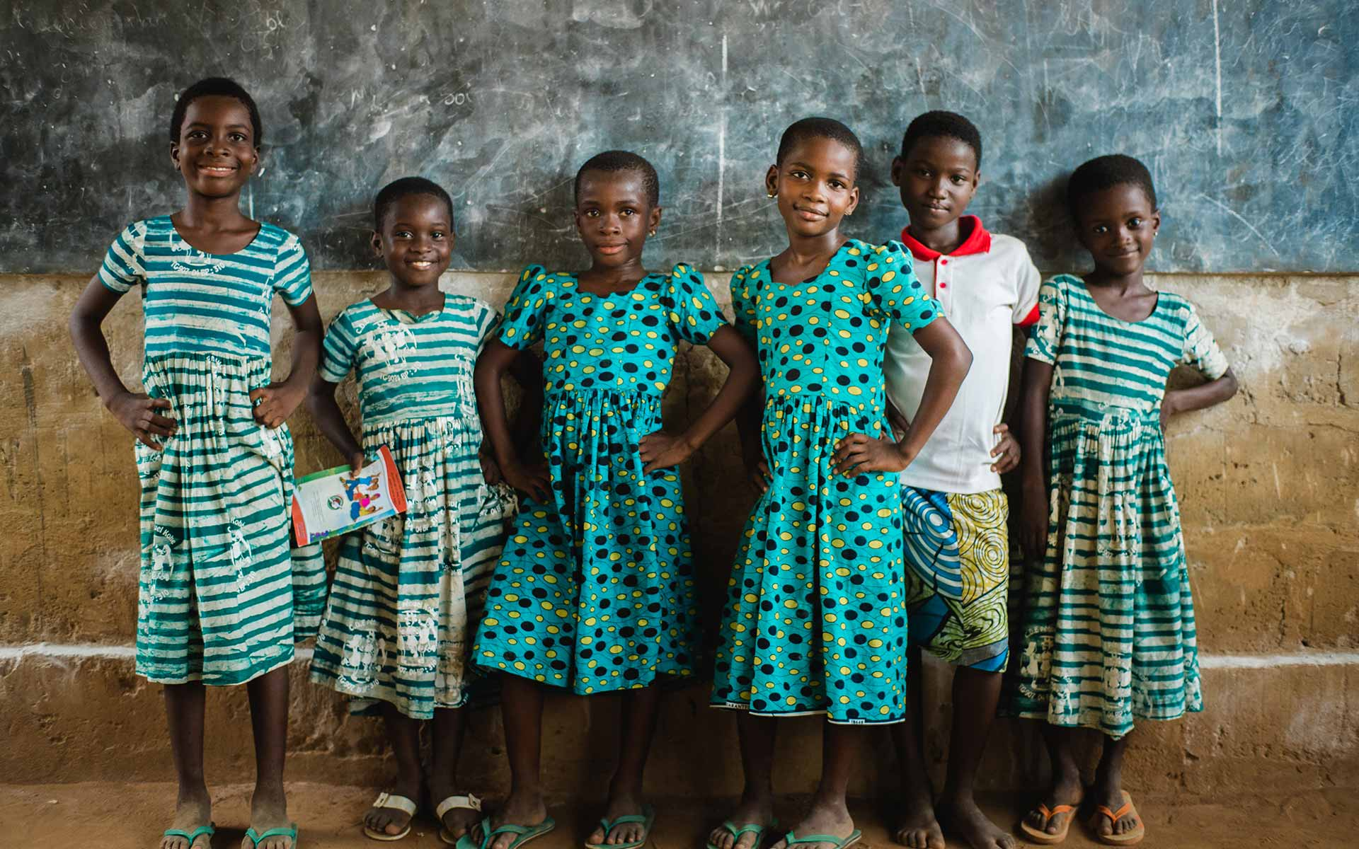 Sponsored children in Togo stand in front of the chalk board in their classroom
