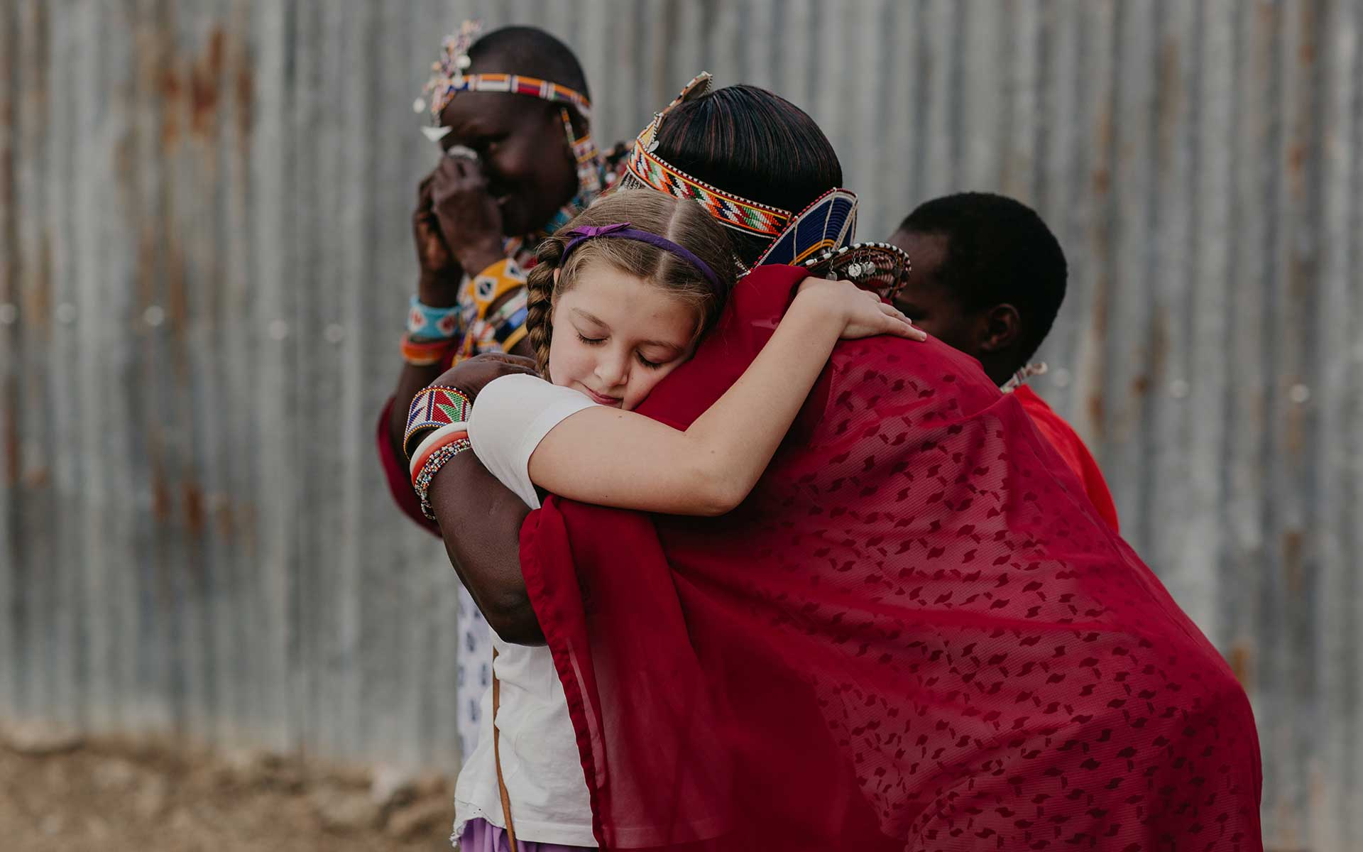 A girl hugs the mother of a Kenyan sponsored child