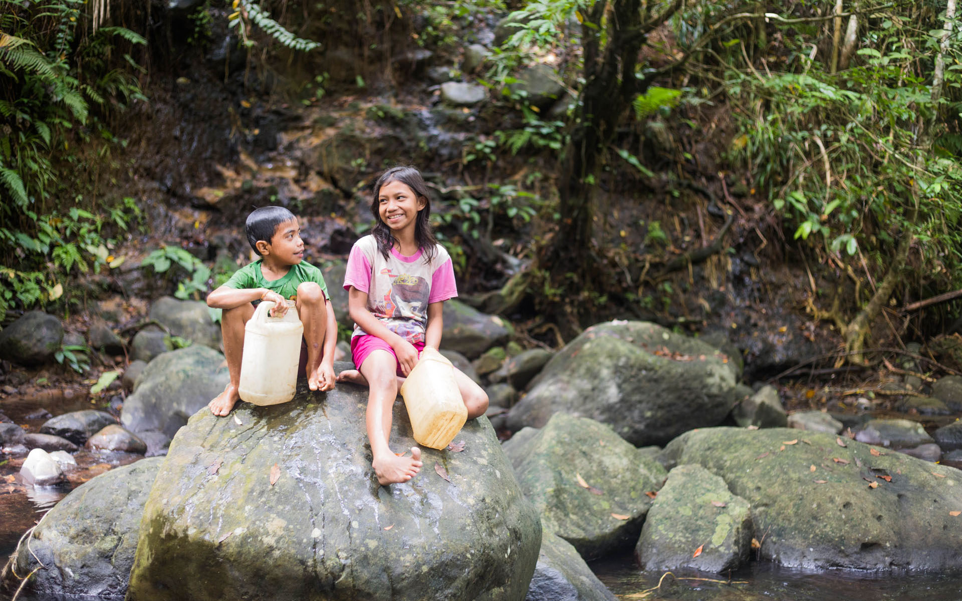 Stevi and Arnold Kusasu collect clean water for their family.
