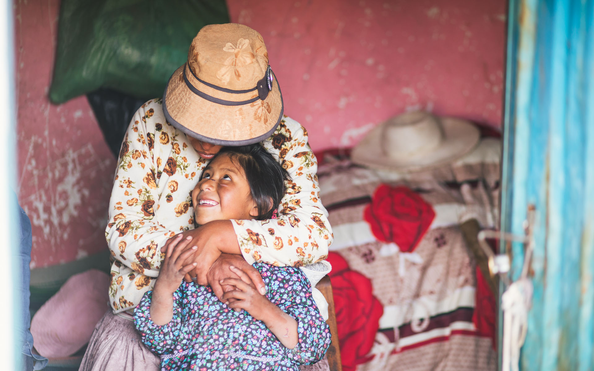 A girl in Compassion's program snuggles up to her mom in their Bolivian home.