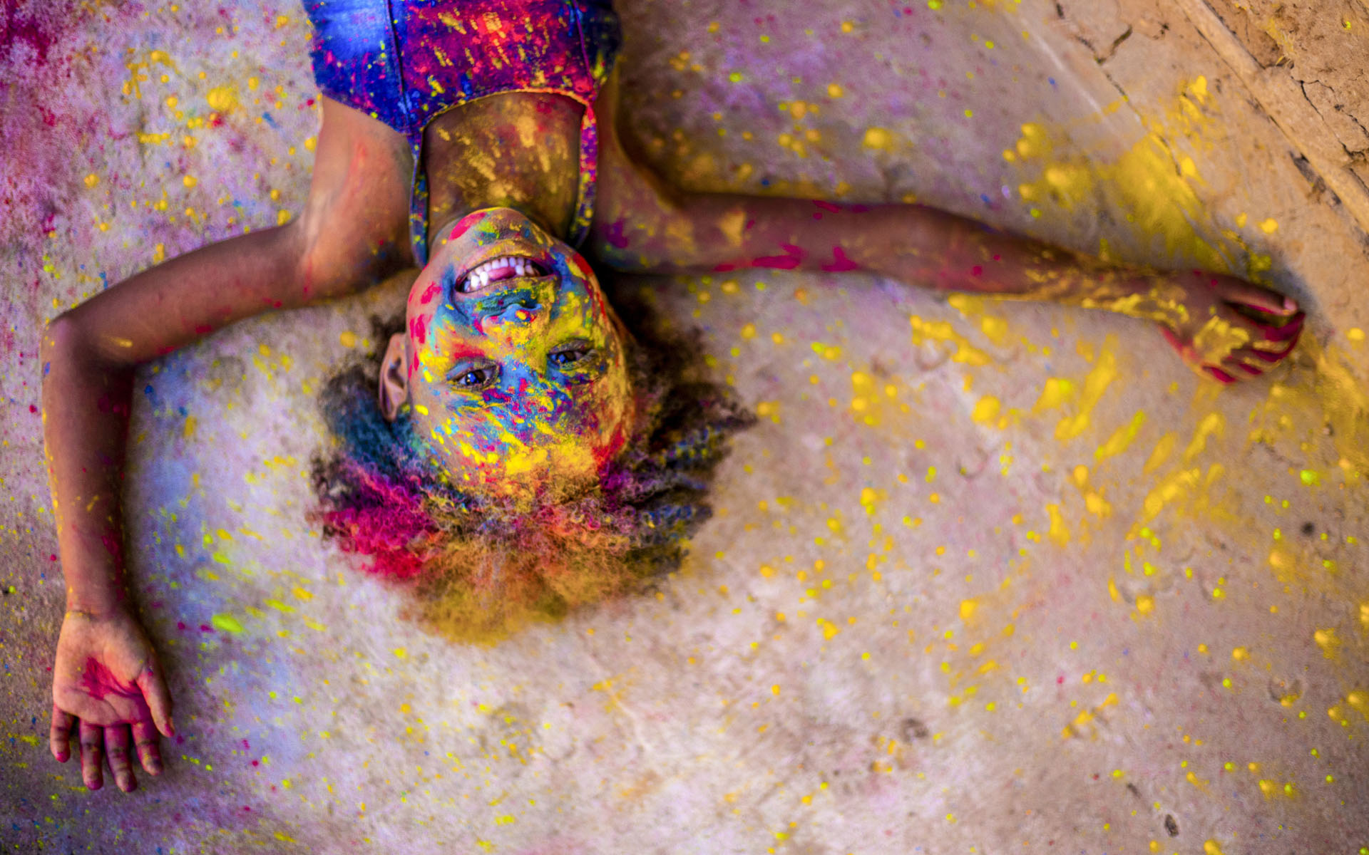 A Brazilian girl is covered in colorful powder outside her Compassion center.