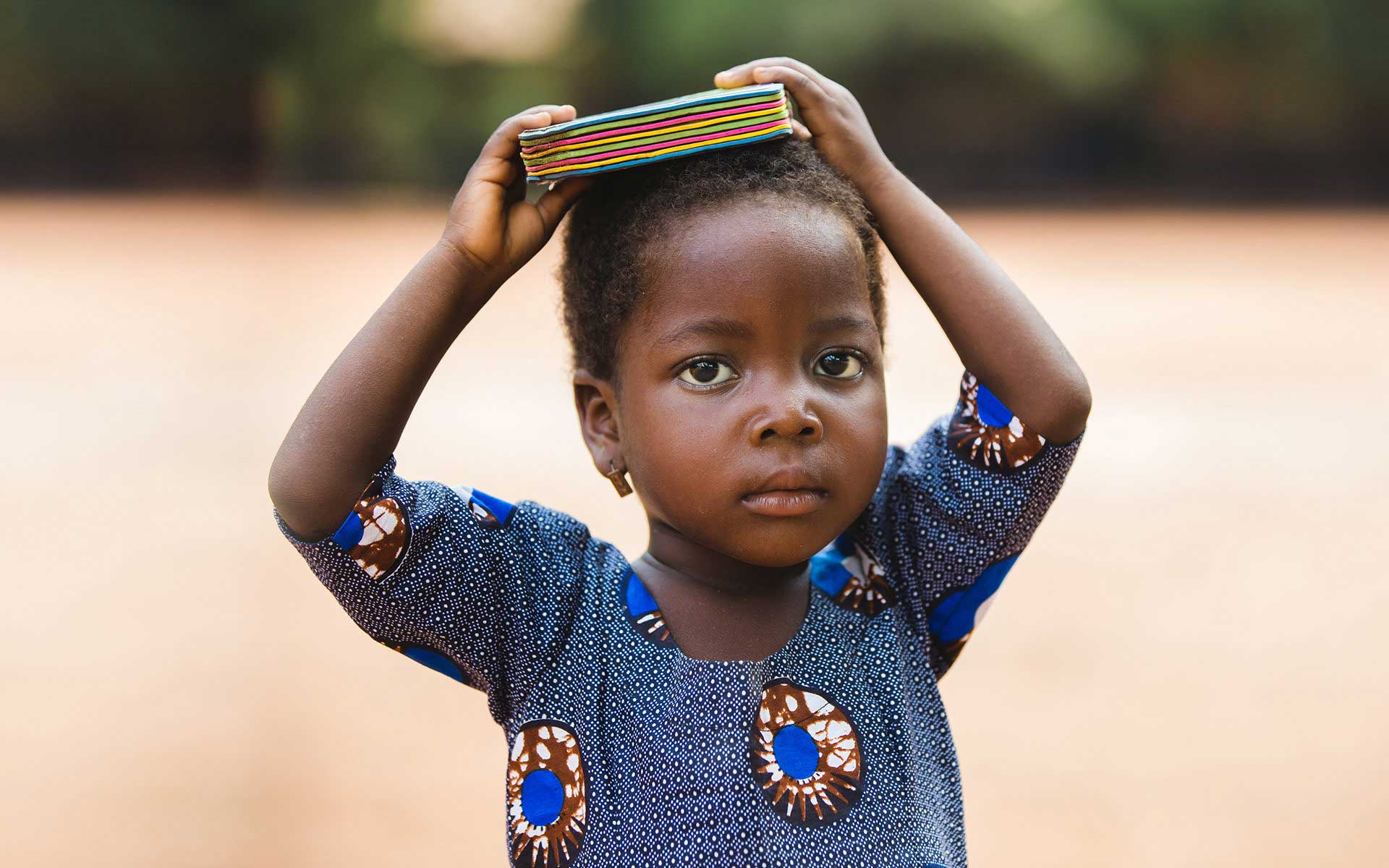 A toddler in Togo holding a book on his head