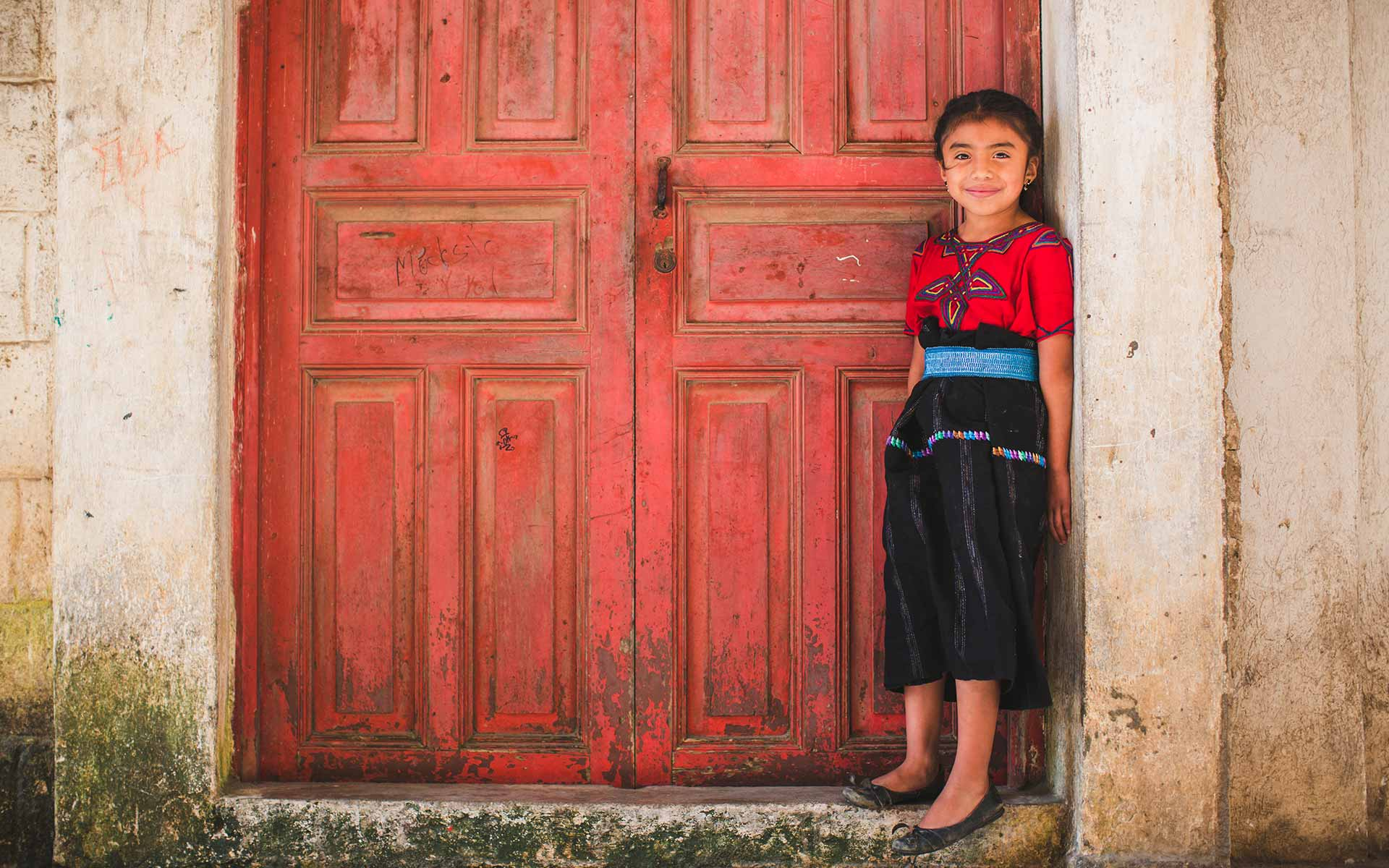 A young girl standing in front of a red door in Guatemala