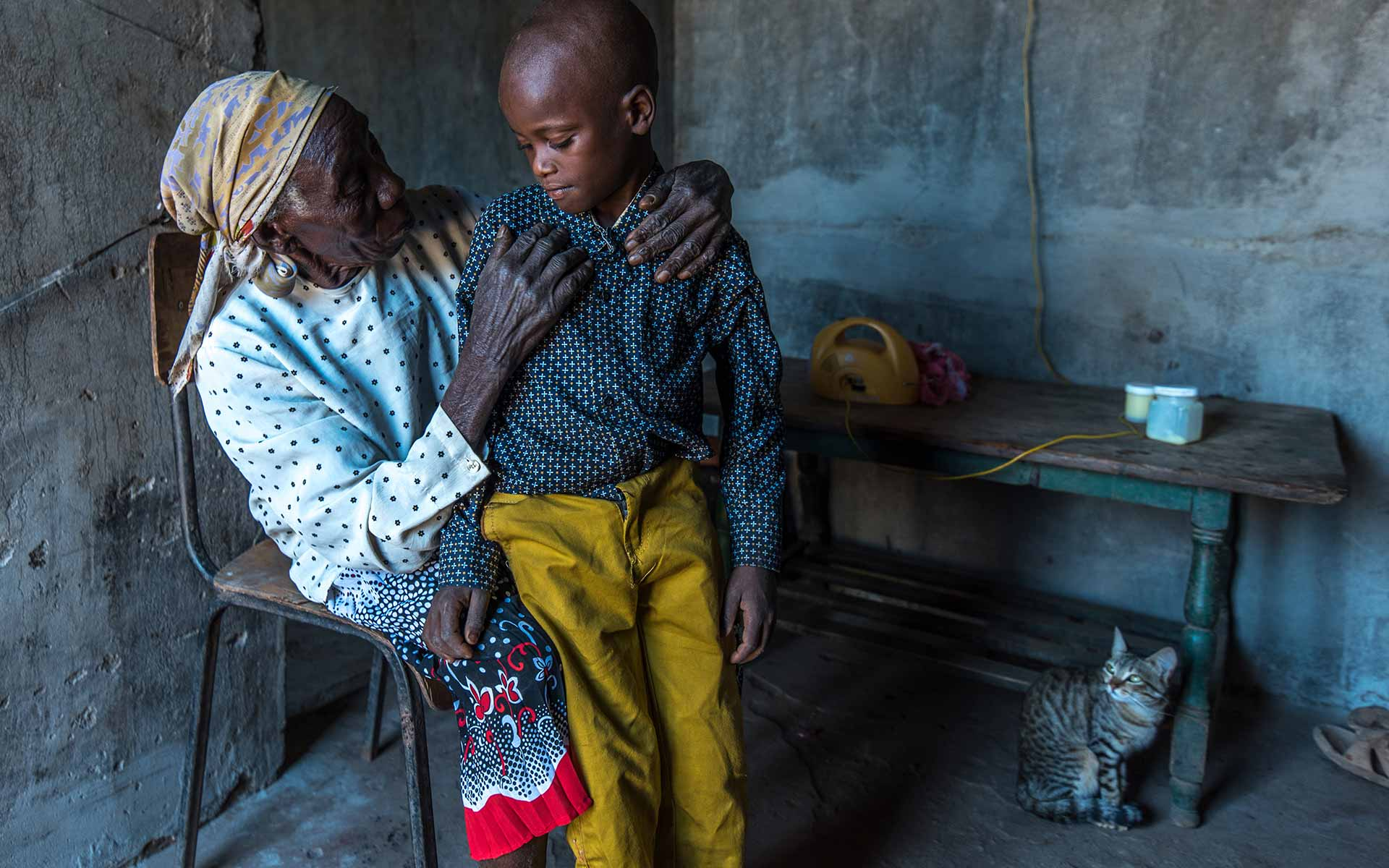 A young boy sits with his grandmother in their home in kenya