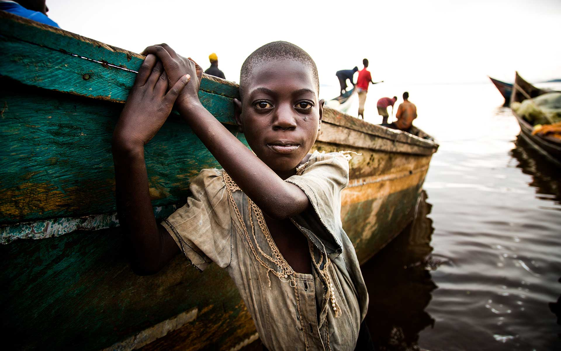A boy plays near a boat in a Ugandan village