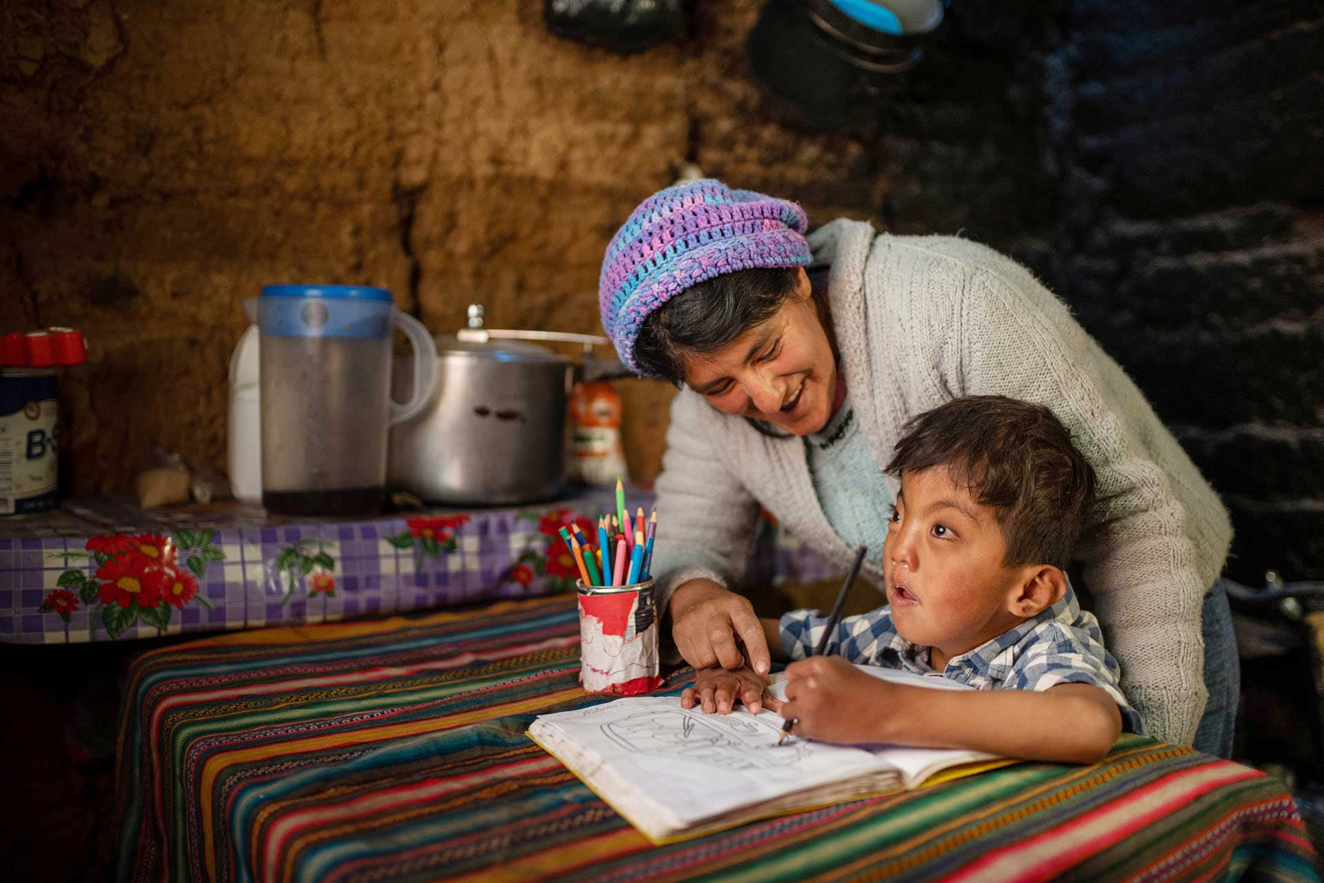 Jesus, 7, draws pictures at home in Peru with his mom
