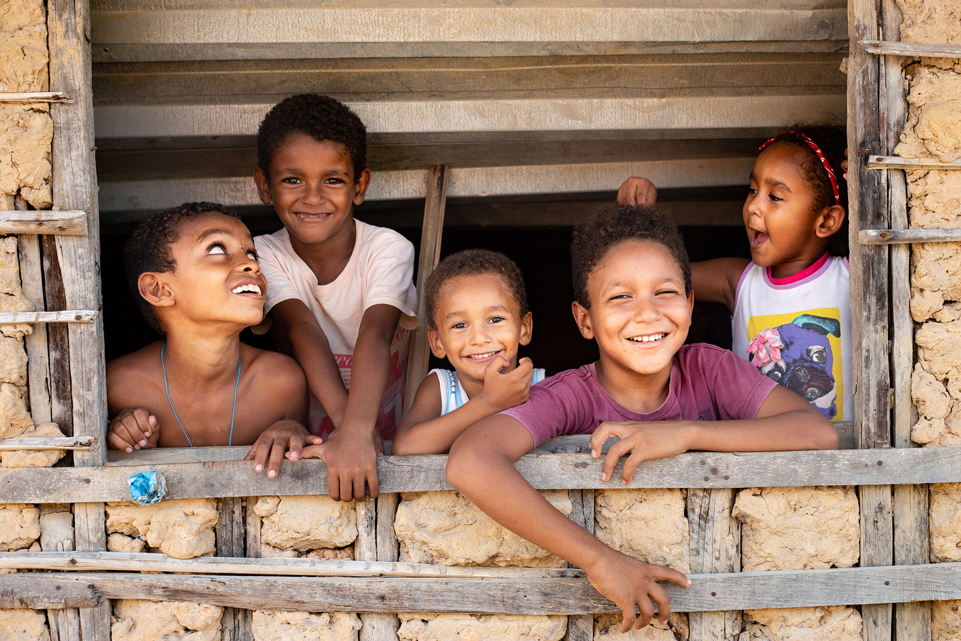 Children in Brazil look out a window in their house