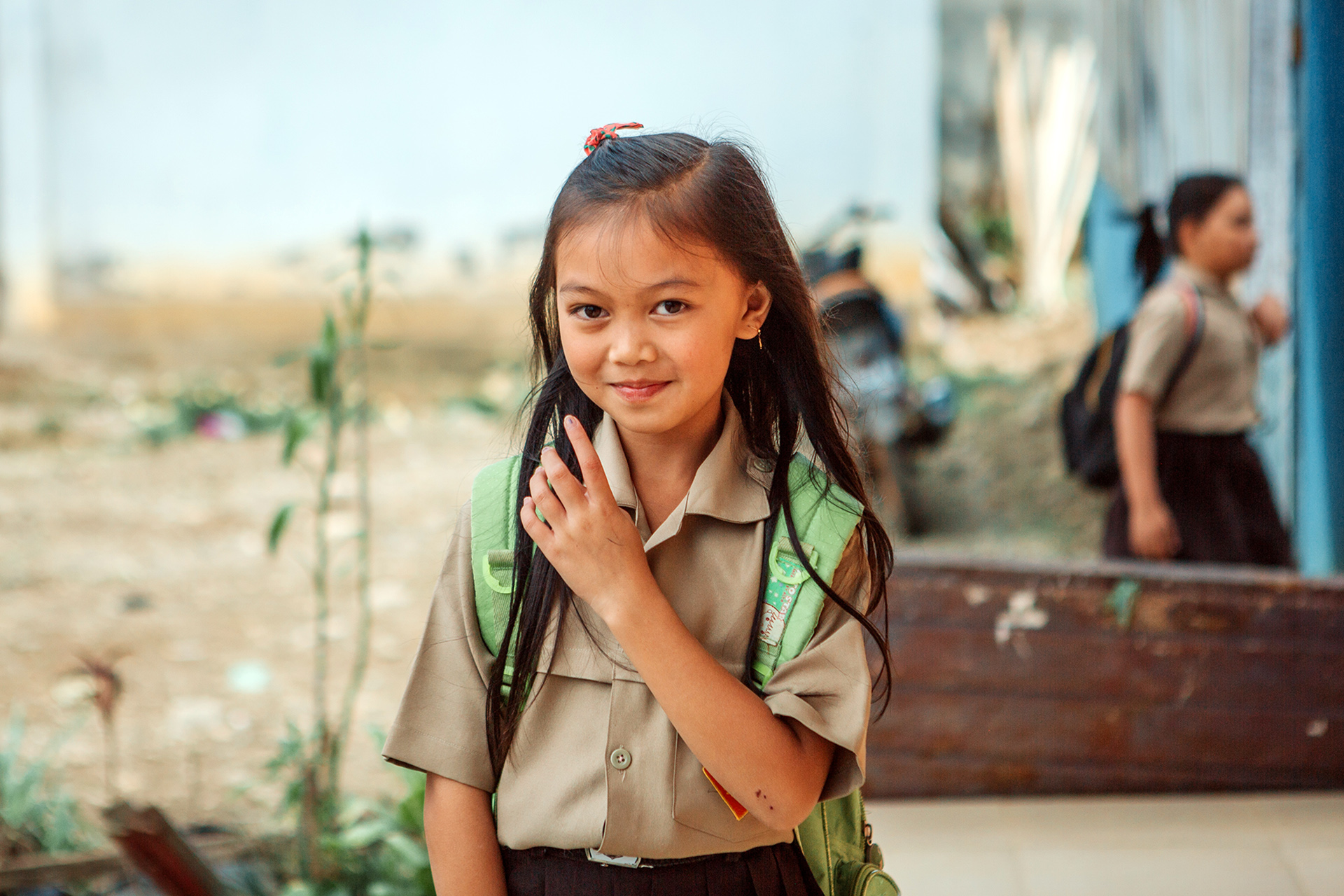 a young girl in Indonesia stands in her school uniform