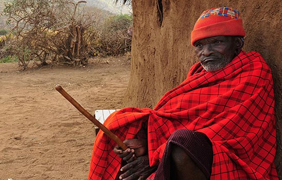 an elderly Maasai man in traditional Maasai garb