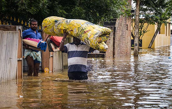 a man carries a mattress on his head while walking in waist deep water