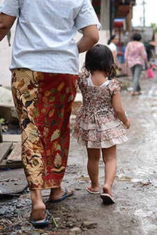 An Indonesian mother and child walk along a muddy street