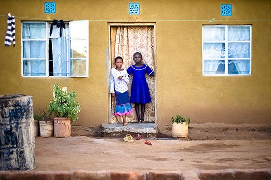 Two African children stand in the doorway of their home