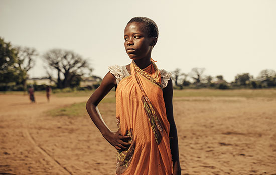 A poor African girl with a serious and dignified expression stands with a hand on her hip