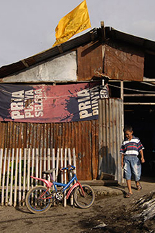 An Indonesian boy is walking out of his house. His bicycle is parked next to a slat fence to his right. The house is covered with tin and tarpaulins for the walls and a tin roof. There is a yellow flag on the roof