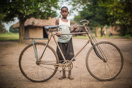 A girl stands behind a bicycle