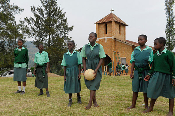 A group of girls playing soccer in front of their church