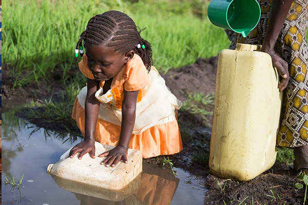 A young girl helping her mother fill water canisters