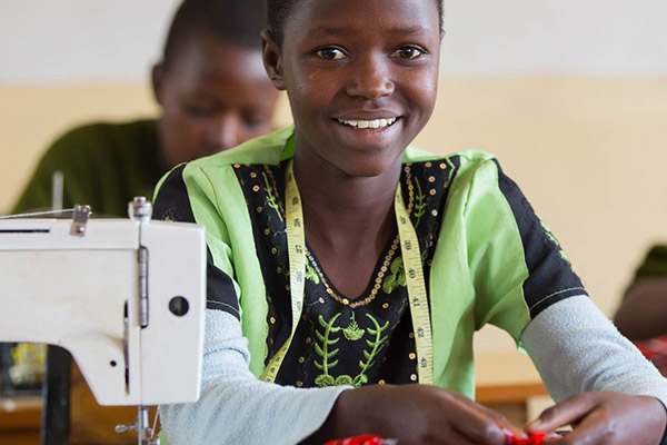 A girl learning to sew as her vocational skill