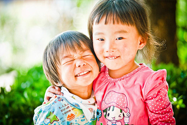 Two young girls embrace and smile