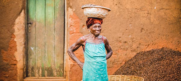 A elderly woman balances a basket on her head