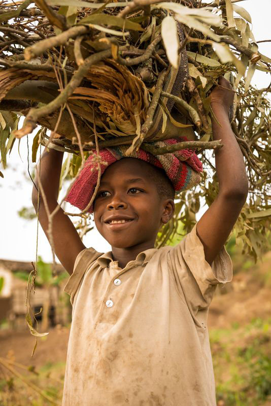 A child carries twigs on her head and smiles