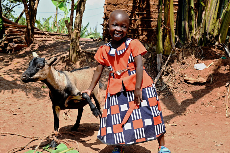A girl smiles with a goat