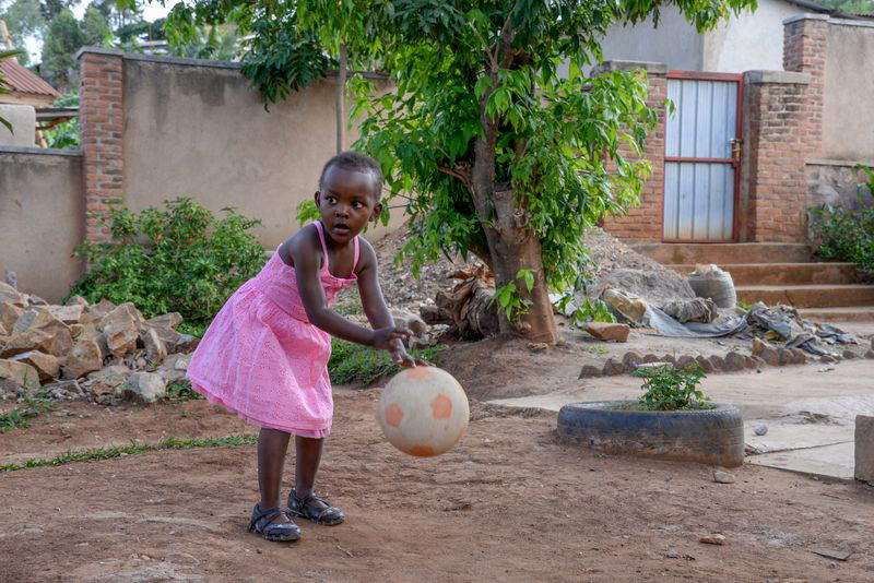 A girl plays with a soccer ball outside her home