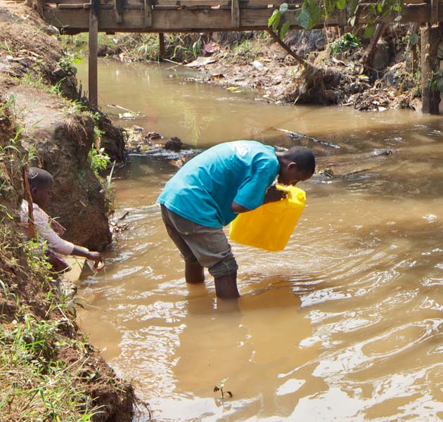 A boy filling his water jug from a local river