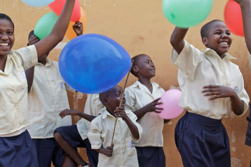 Children laugh and play with balloons