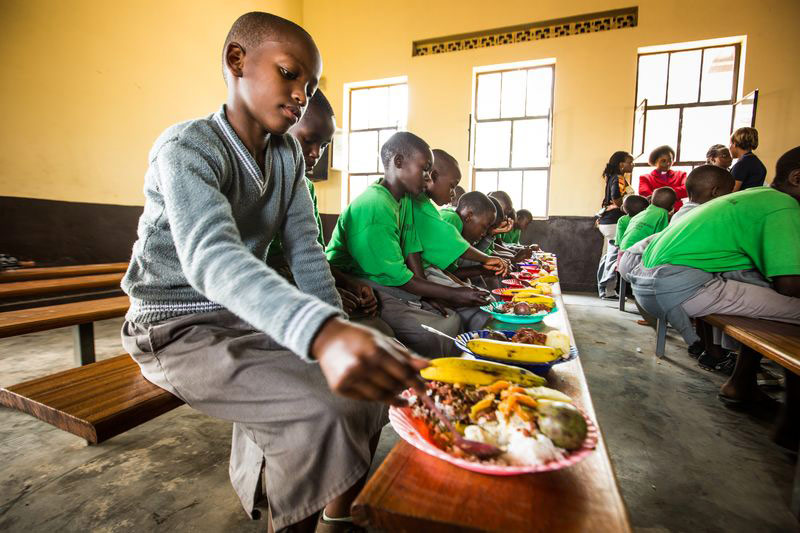A group of children eat a delicious meal they received at their child development center