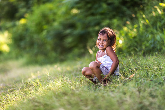 A young Indonesian girl sits in the grass