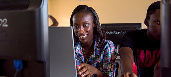 A young woman working in front of a computer screen