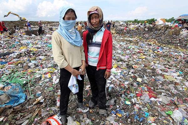 Sisters standing in the city dump