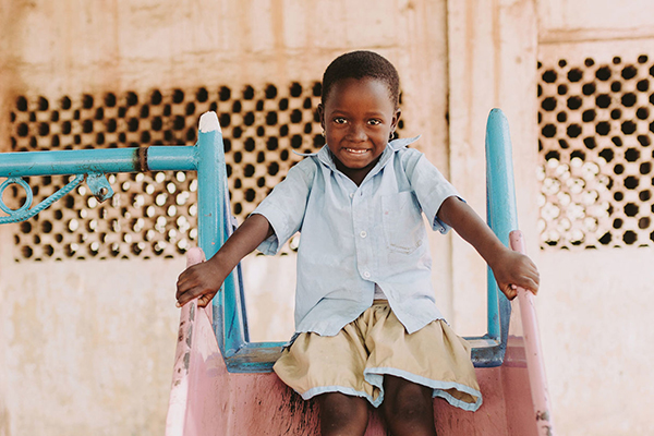 Aklobessi smiling as she goes down a slide at her Compassion center in Togo