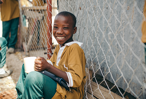 Smiling boy sitting by a fence holding a mug