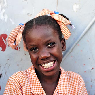 Sponsor a child today! This smiling girl in Haiti is laughing and wearing a red checked dress with a matching hair bow. How can your child sponsorship contribution help a girl like her? Your generous support provides medical check-ups, nutritious food, educational assistance and access to special services like surgeries and disaster relief. In addition, the child you sponsor has the opportunity to hear the good news of Jesus Christ.