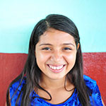 a smiling salvadoran girl living in poverty