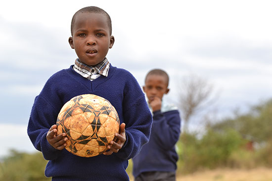 A young Kenyan boy in a blue sweater holds a soccer ball