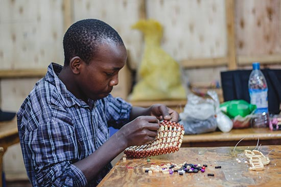 a boy doing beadwork