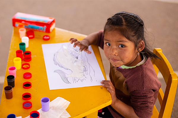 A young girl in Bolivia paints with her fingers