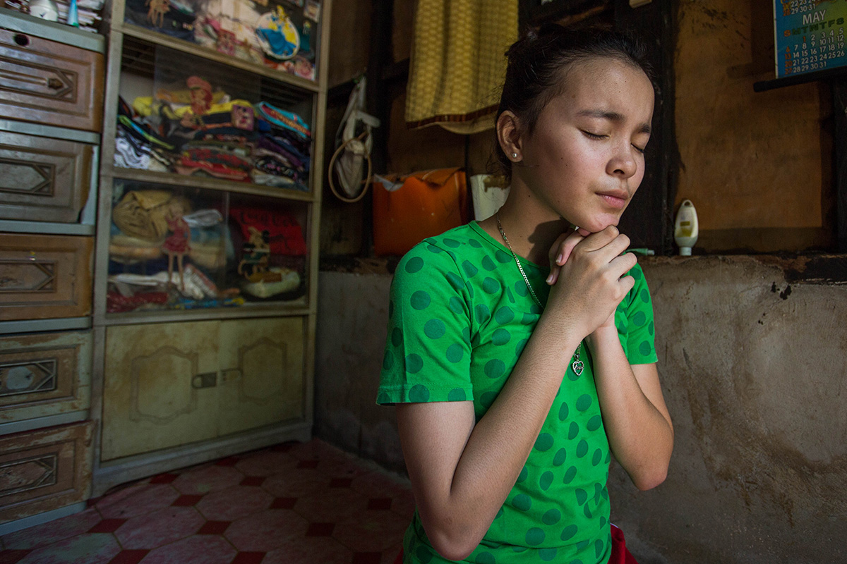 Bea prays in her home